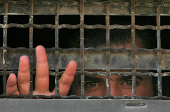 Photo: A Palestinian prisoner looks out of a military truck as he leaves the Ketziot prison camp in southern Israel, Tuesday, Oct. 2, 2007. Israel sent 29 Palestinian prisoners back to the Gaza Strip on Tuesday, completing a release meant as a goodwill gesture ahead of a U.S.-sponsored Mideast peace conference this fall. (AP Photo / Tsafrir Abayov)