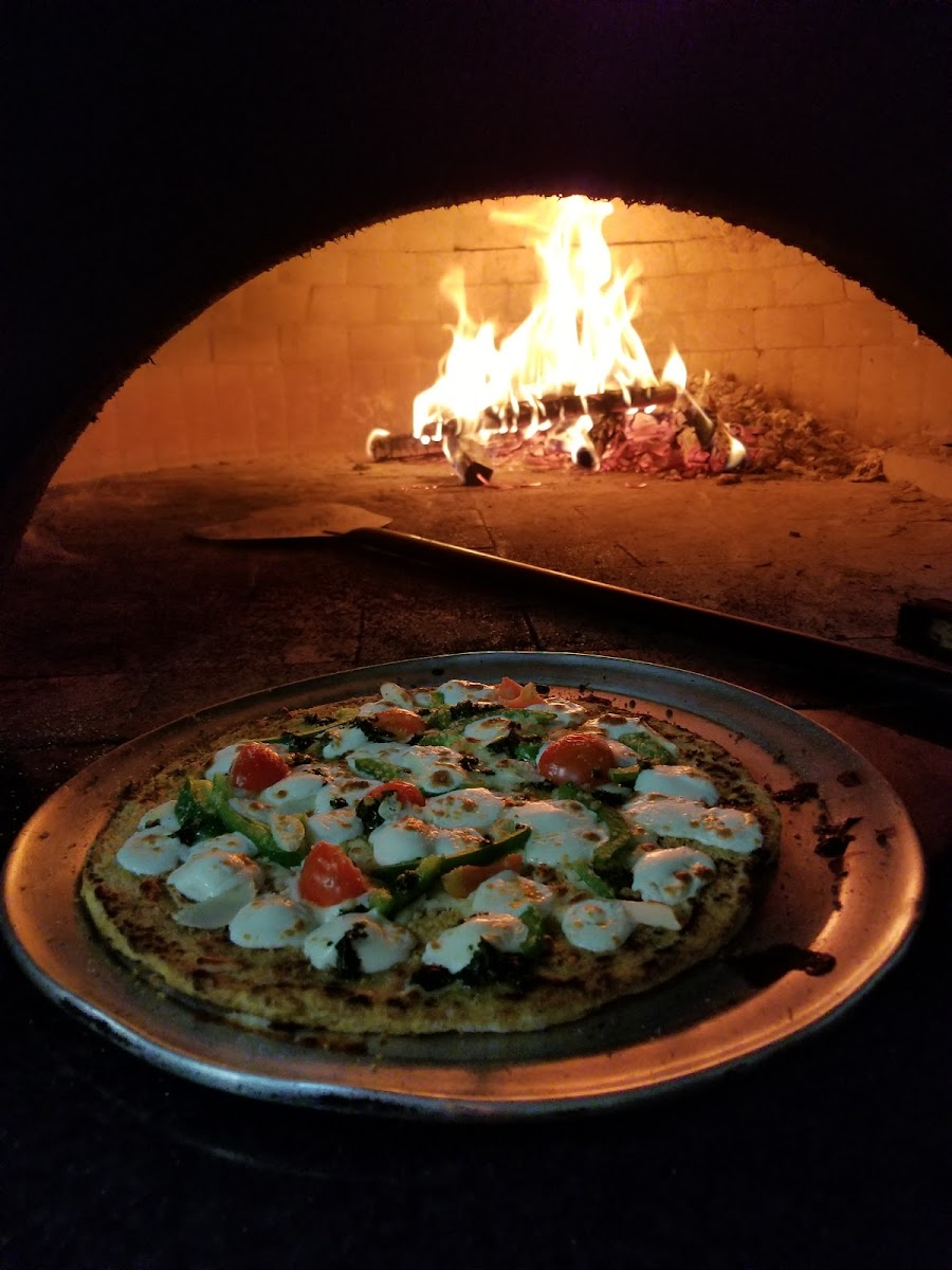 Delicious, gluten free Cauliflower Pizza made in a wood burning pizza oven.