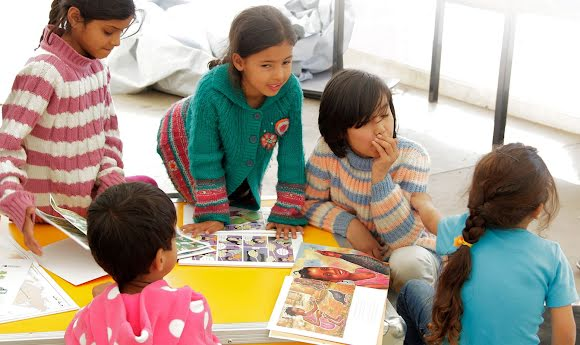 Five refugee children huddle around an Ideas Box reading picture books.