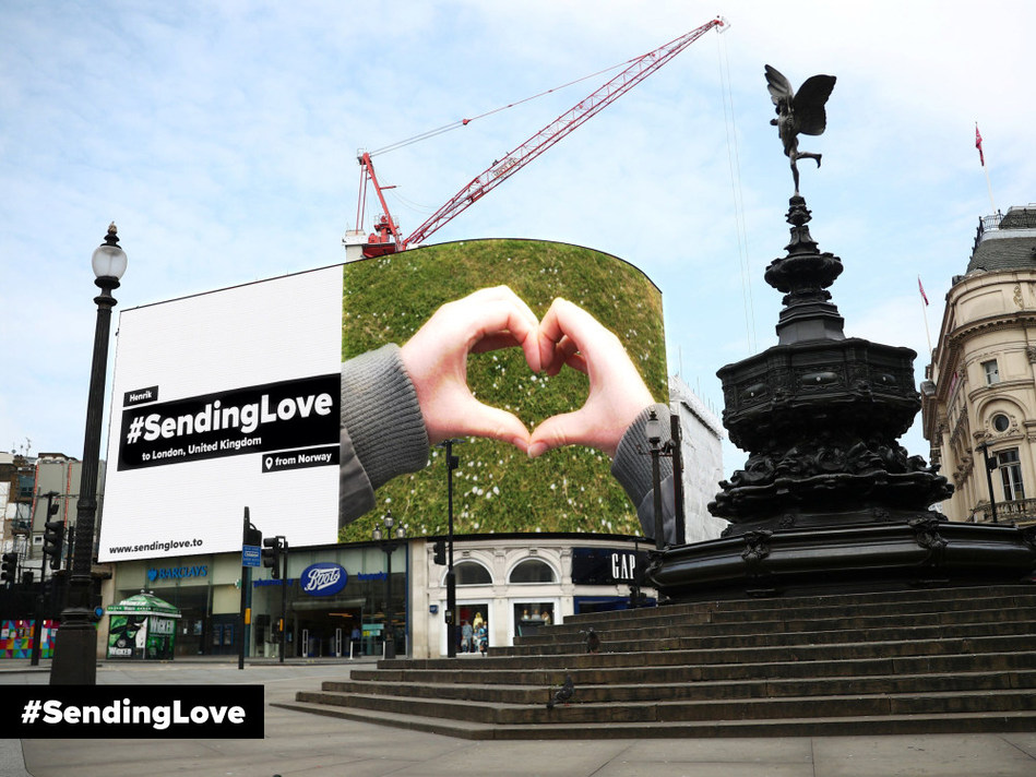 """Giant digital billboard showing a photo of 2 hands making a heart and  the message on teh left saying """"#SendingLove to London, United Kingdom, from Norway"""""""