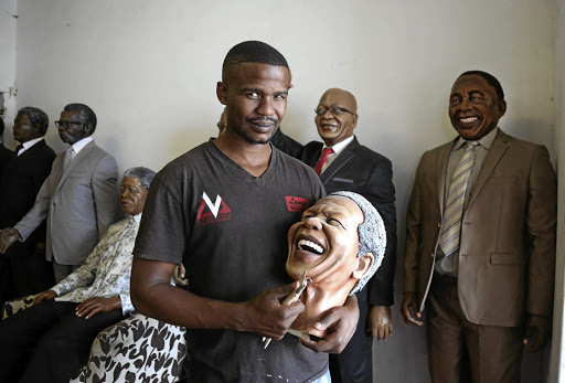 Wax sculptor Lungelo Gumede holding a cast of Madiba.