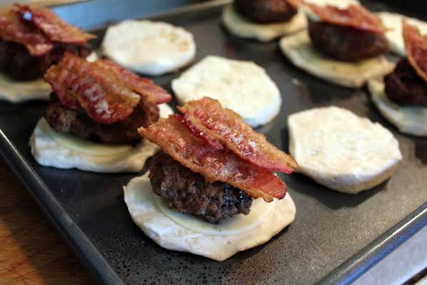 Bacon on top of a hamburger patty.