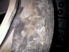 Photo: File miles from the end of our five-hour drive, we run into a pothole.  Our tire doesn't thank us.