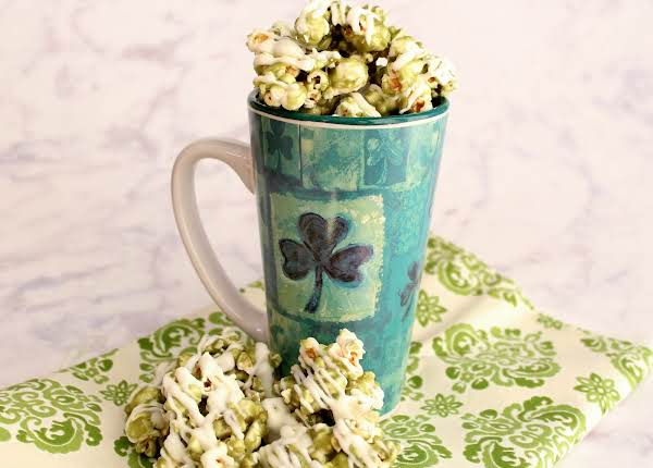 Toffee Popcorn In A Cup With Popcorn Scattered Around.