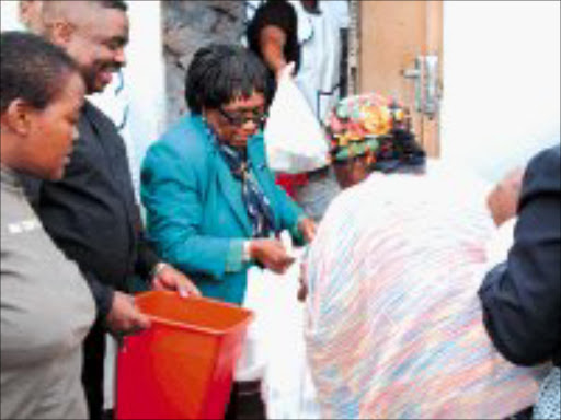 GIVING HAND: Marjorie manganye hands out food hampers to the elderly while staff members and sponsors look on appreciatively. Pic. Lindi Obose. © Sowetan.