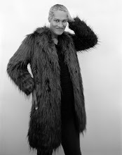 Black and white portrait photograph showing me with short bleached hair in a faux fur coat