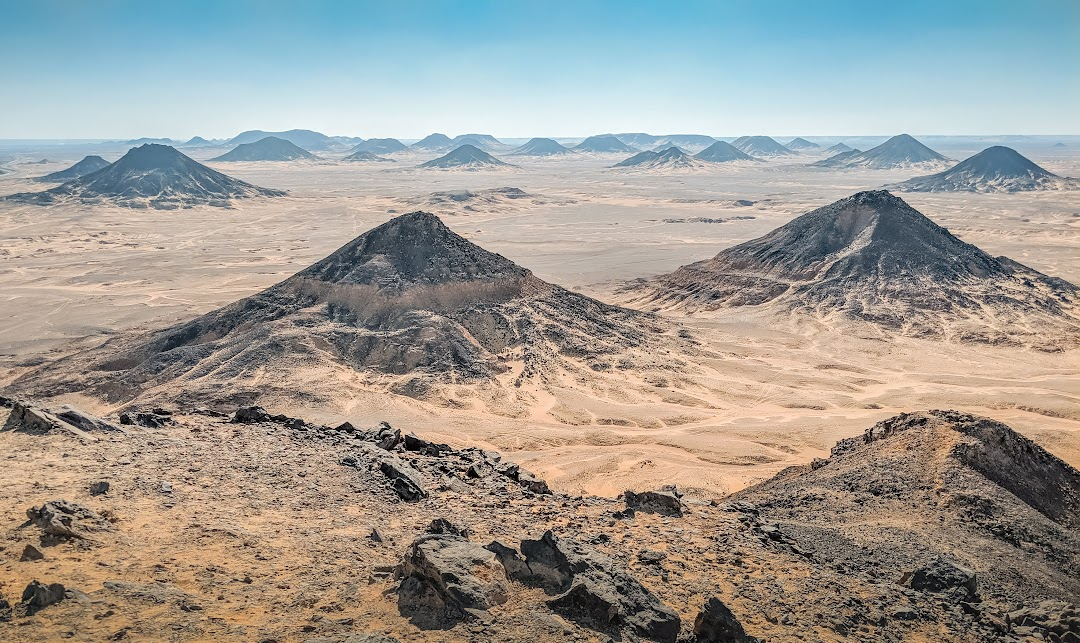 A landscape of black peaks on flat desert.