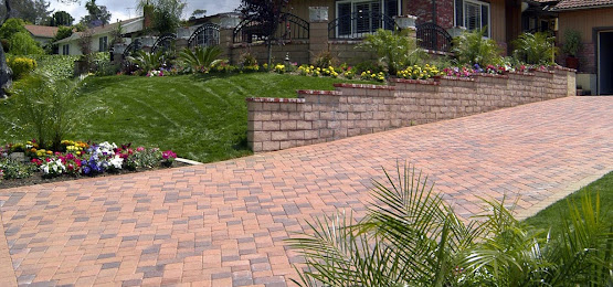 a driveway with redbricks next lush green grass