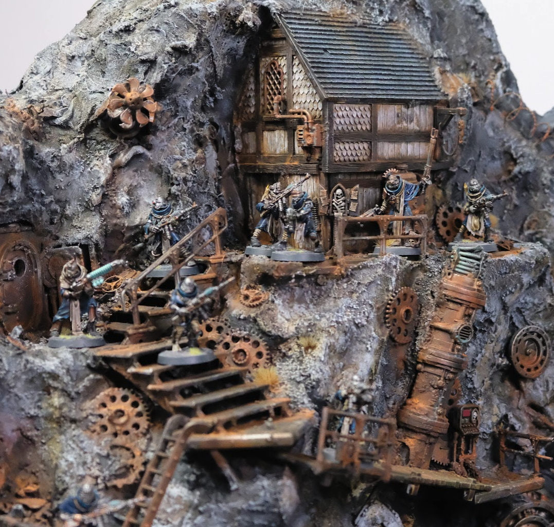 A diorama of 28mm ad mech miniatures descending from a wooden house embedded in dust and rusted junk