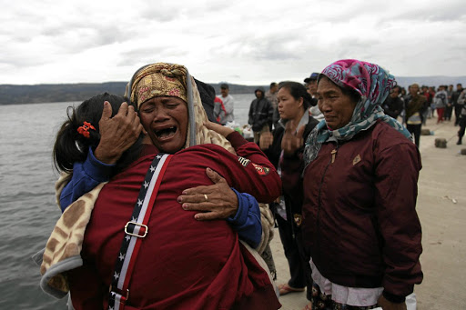 Relatives cry while waiting for news on missing family members who were on a ferry that sank on Monday in Lake Toba, at Tigaras Port, Simalungun, North Sumatra, Indonesia. REUTERS/Albert Damanik