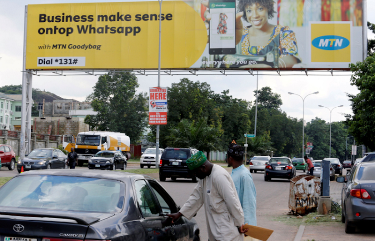 People stand near an advertising billboard for MTN along a street in Abuja, Nigeria, September 4 2018. Picture: REUTERS/AFOLABI SOTUNDE