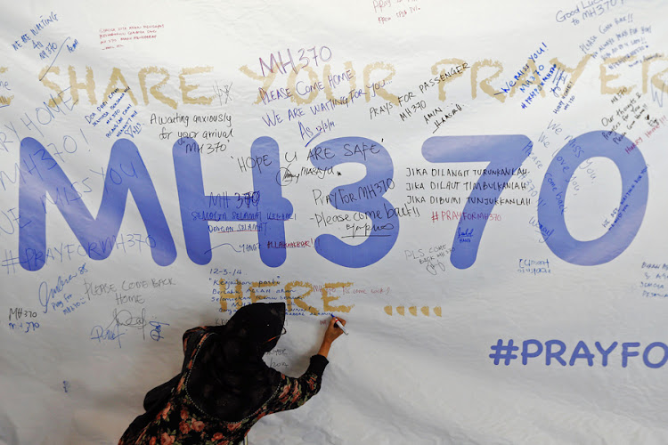 A woman writes a message of hope for the passengers of the missing Malaysia Airlines flight MH370 on a banner at Kuala Lumpur International Airport. Picture: REUTERS