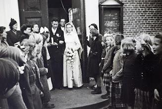 Photo: Bruidspaar Teunis Rozenveld enTinie kamping Rd. verlaten de kerk. Achter hen staat dominee Van Wezep.