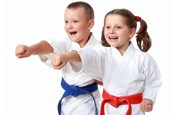 2 children wearing karate uniform showing their punches while smiling.