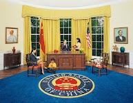 Chinezen in het 'oval-office van China': president aan telefoon met secretaresse ernaast, echtgenote met kind vóór het bureau en Mao Zedong en Abraham Lincoln op schilderijen