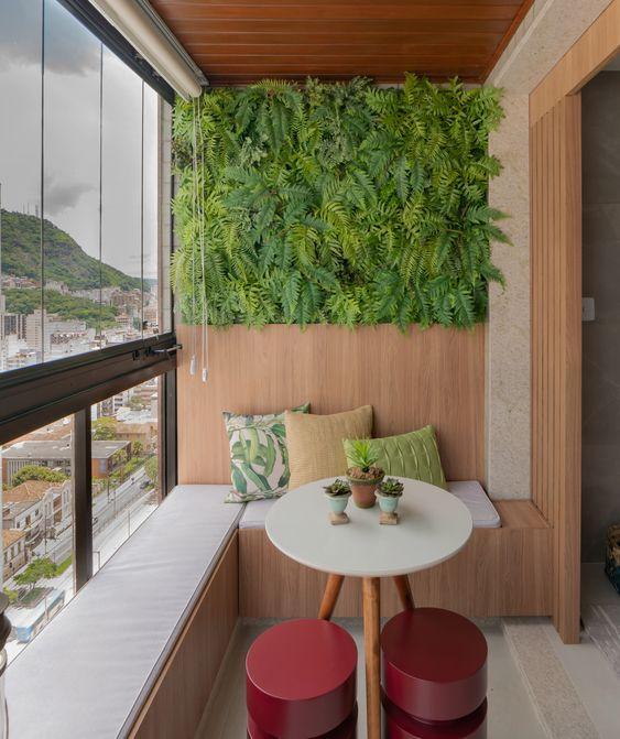 Varada em estilo moderno com teto de madeira, painel de madeira na parede com jardim vertical, móvel de madeira com estofado branco e mesinha de centro redonda com banquinhos vermelhos.