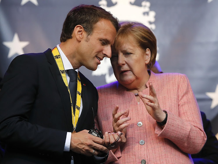 French President Emmanuel Macron speaks to German Chancellor Angela Merkel after being awarded the Charlemagne Prize during a ceremony in Aachen, Germany, May 10 on 2018. Picture: REUTERS