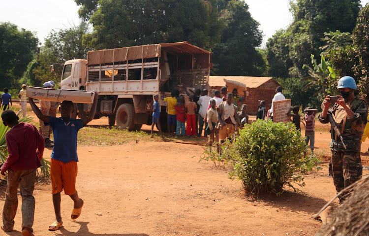 Civilians offload electoral materials from a United Nations Multidimensional Integrated Stabilization Mission in the Central African Republic (MINUSCA) truck, ahead of the upcoming elections in Yongofongo, Central African Republic on December 17, 2020.