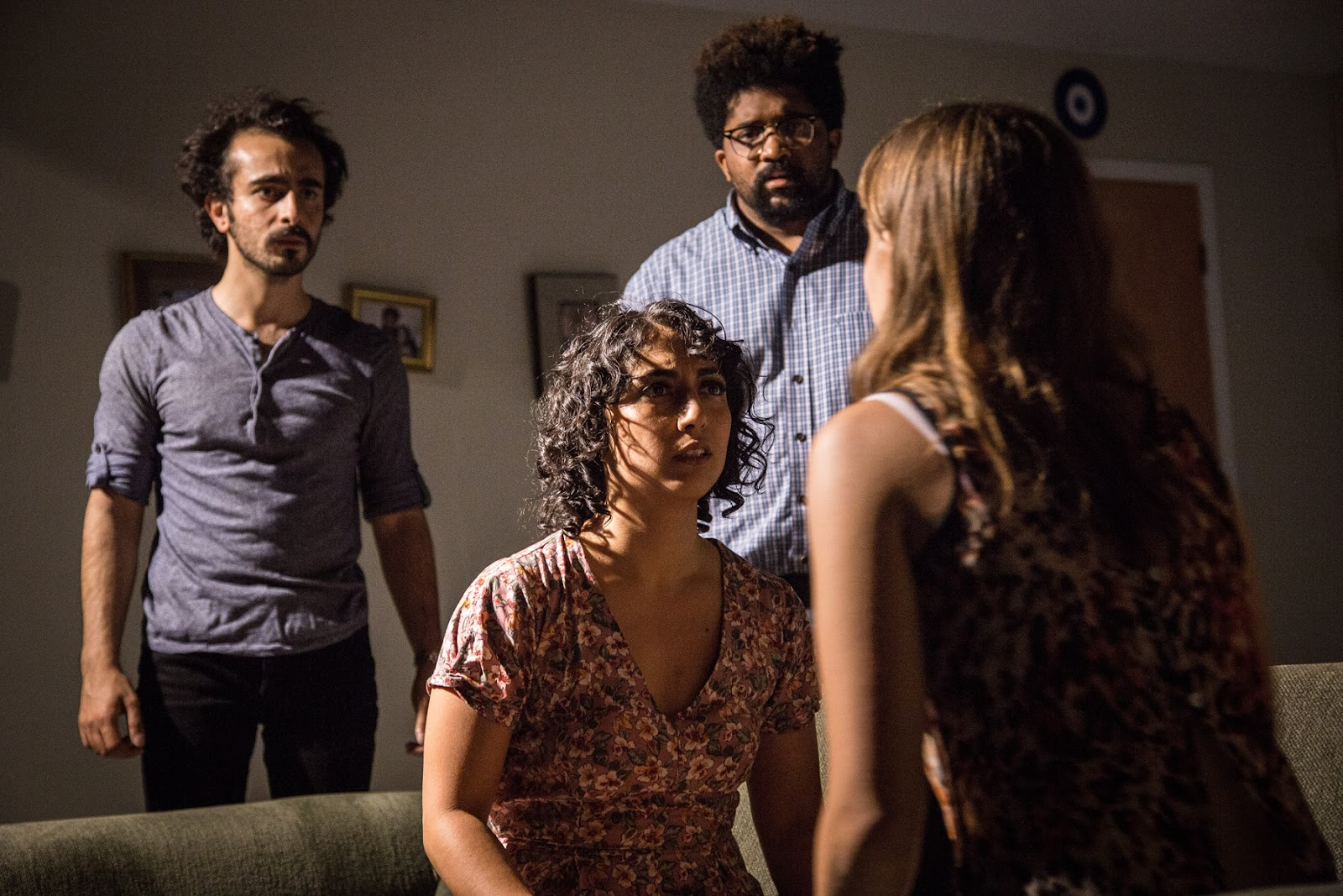"Image: The cast of ""KISS."" In the background Salar Ardebili stands to the left, Arti Ishak sits center, and Monty Cole stands to the right. They all face Cassidy Slaughter-Mason in the foreground whose back is to us. The walls behind the three have three photos and a door to the right. Image courtesy of Austin D. Oie."