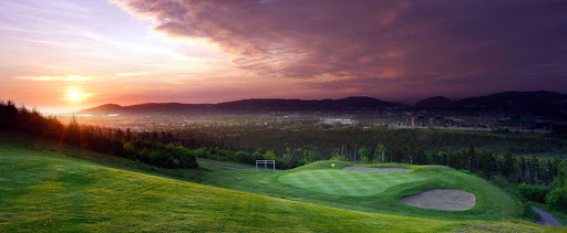 A breathtaking sunrise overlooking a golf green and the distant mountains on Avalon Peninsula, Newfoundland.