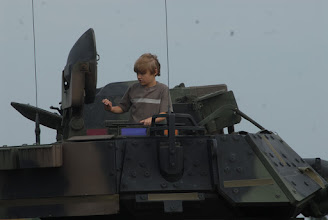 Photo: A child opens the hatch to a Bradley Fighting Vehicle.