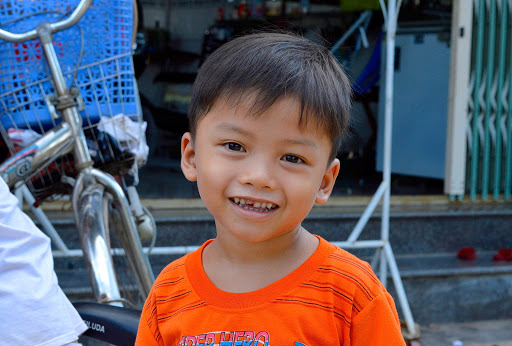 A young boy very happy to see Western tourists visit his village in Vietnam.