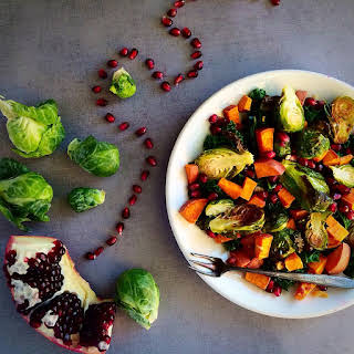 Warm Kale Salad with Pomegranate and Garlic Roasted Brussels Sprouts and Sweet Potatoes.