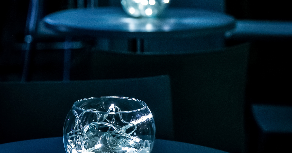 A glass centerpiece featuring a string of white lights at a gala event