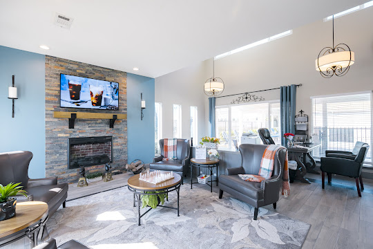 Clubhouse with wood-inspired flooring, seating, and fireplace