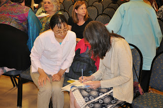 Photo: Elizabeth Carroll Hayden signs a copy of the anthology for Qiaolan Wan.
