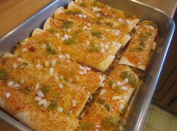 Once all enchiladas are rolled, pour the remaining can of enchilada sauce over tortillas,...