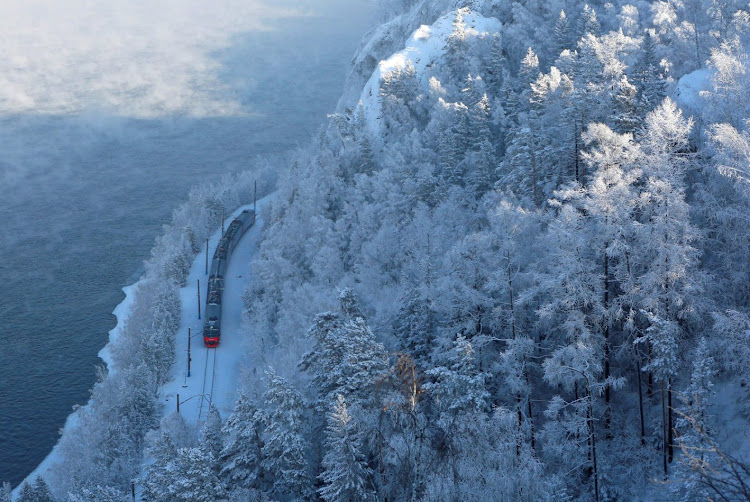 A passenger train along the bank of the Yenisei River in the Siberian Taiga in Russia.