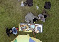 Aerial image of Congolese artist Mugabo working with friends on his mixed media piece.