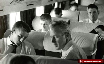 Photo: Wilkinson sitting among the players during a team flight. Date unknown.