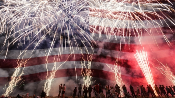 Fireworks exploding in front of an enormous American Flag with people standing in the foreground watching the display.