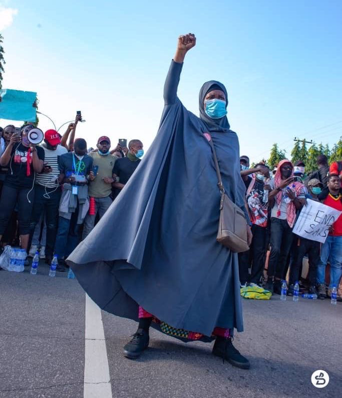 Aisha Yesufu standing in front of fellow endsars protestors, with one fist raised.