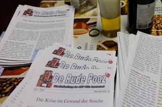Auf einem Tisch liegt ein Stapel «De Rude Pooz», daneben steht etwas zu trinken.
