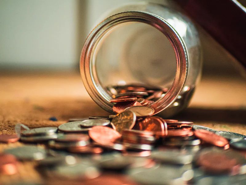Photo of a jar on its side with coins spilling out
