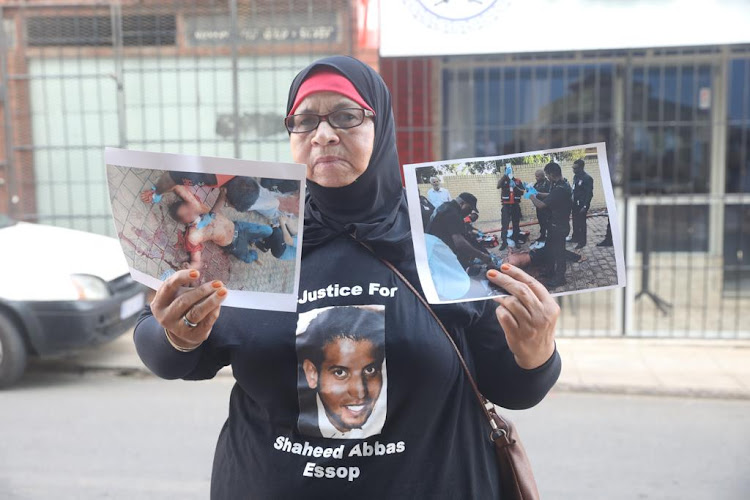 The mother of Shaheed Abbas stands in silent protest outside the Verulam magistrate's court, where the men accused of killing her son in a mosque attack appeared on Friday, February 22