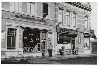Photo: 1935 Bredascheweg gezien vanuit het zuidwesten. De panden respectievelijk Huis van Negotie van J.M. Pinxteren en G.J. de Rooij's rijwielhandel.