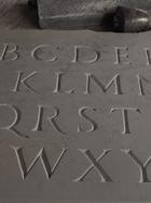 Lettres gravées sur pierre en creux au ciseau sur pierre calcaire polie