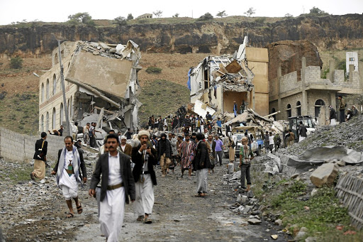 People walk near the site of a Saudi-led air strike in Sanaa, Yemen. Picture: REUTERS