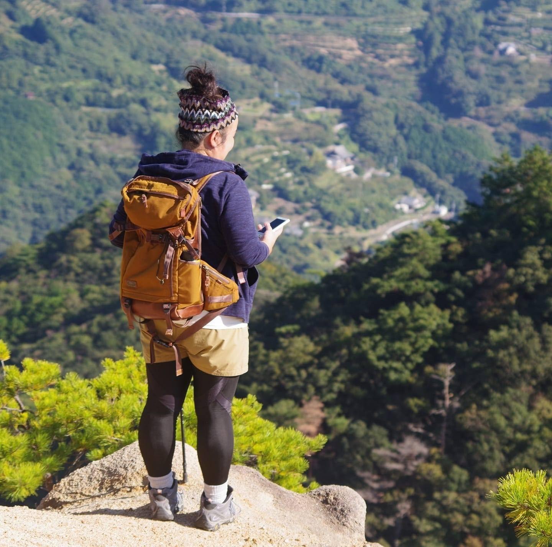 岩山を歩いている女性  中程度の精度で自動的に生成された説明