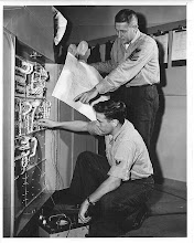 Photo: May 1958 Cliff Bosworth, TD2 and Billy Brawblett, TD1 check out a circuit in the new F9F-8T Cockpit Proceedures Trainer in the Ground Training Dept.