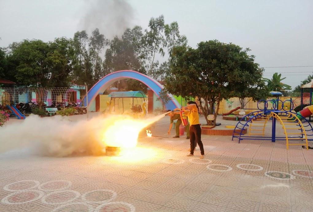 Cán bộ, giáo viên thực hành sử dụng bình chữa cháy dập lửa.