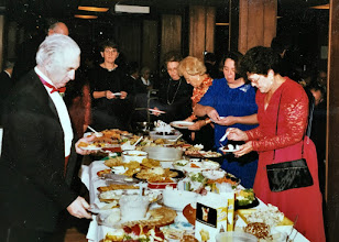 Photo: A pitch-in buffet was added to the December Dance for the 20th Anniversary Celebration.  Left to right: Dick Pendleton with the red bowtie.  Ernie Kendall is looking at the camera from the end of the table (John's head is to her right).   Imogene Royal in black with the long necklace.  Peggy Cassens is in the shiny blouse.  Mary Ellen Eldridge in the blue dress.  That is Marty (?) in the red dress.  The buffet remained a December tradition until we added the New Years Dance (and needed nourishment to make it to midnight).