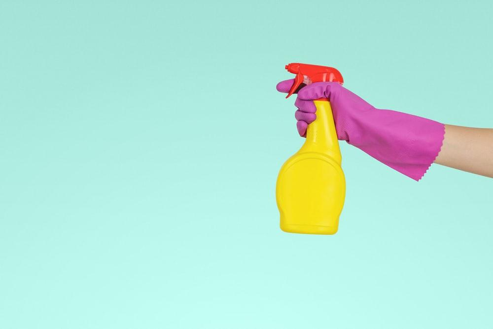 person holding yellow plastic spray bottle