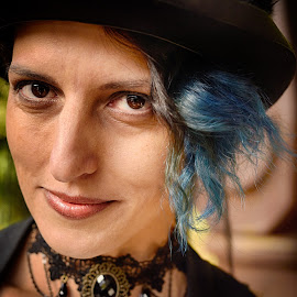 Charming Roberta by Marco Bertamé - People Portraits of Women ( looking into camera, spotting, woman, blue, steampunk, headshot, looking, hat, portrait, eyes, watching )