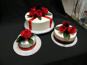 Photo: Red & black accented wedding cakes featuring smooth whipped cream icing, black feathers, red roses & black/red ribbon wrap.