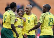 Bafana Bafana star striker Percy Tau (C) celebrates with teammates after scoring a fourth goal during the 6-0 2019 Africa Cup on Nation romp over Seychelles at FNB Stadium in Soweto, south west of Johannesburg, on October 13,2018.